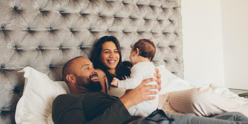 Two parents holding their toddler in their bed bug-free bed.
